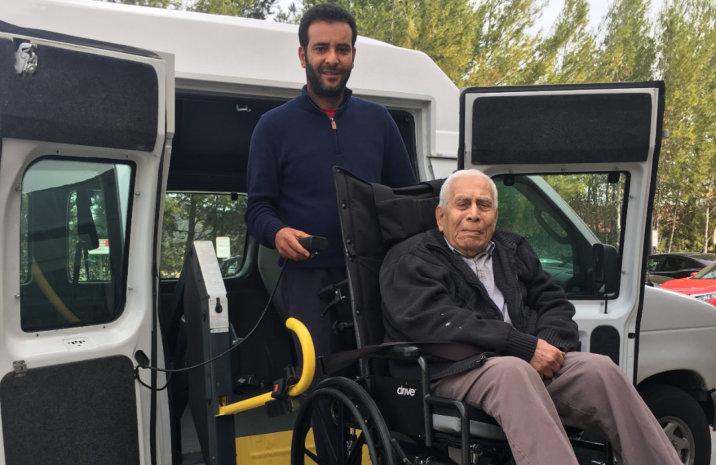 man helping a senior on wheelchair