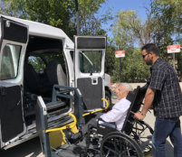 man pushing a man sitting on a wheelchair